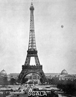 ******** Eiffel Tower, Paris. Early photograph, dating from after the completion of the Eiffel Tower (1889), in Paris, France, with a flag at the top of the tower. A balloon is at upper right. This wrought iron tower, 324 metres tall, was built as the entrance arch for the Universal Exposition (World Fair) of 1889 (buildings in background). At the time, it was the tallest structure in the world. In the foreground is the Pont d'Iena, over the River Seine. The photographic printing technique used here was halftone printing, with the resulting print known as a halftone. This technique became successful in the early 1880s. This is one of the first such prints.