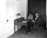 ******** Longitude determination. US astronomer George Andrews Hill (right, 1858-1927) listening to time signals from Paris, France, as part of longitude determination at the US Naval Observatory, Washington DC, USA, in August 1913. The Arlington (USA) and Eiffel (France) towers were used for transmitting such signals across the Atlantic, part of co-ordinating the official timing and co-ordinate systems. Photographed in the passageway to the south transit house at the US Naval Observatory.