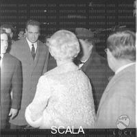 ******** Fellini e Giulietta Masina (quest'ultima di spalle) in via Bissolati per la prima del film 'Otto 1/2' - piano medio. Prima del film 'Otto e 1/2' di Fellini al cinema Fiamma. via Bissolati a Roma. 13.02.1963